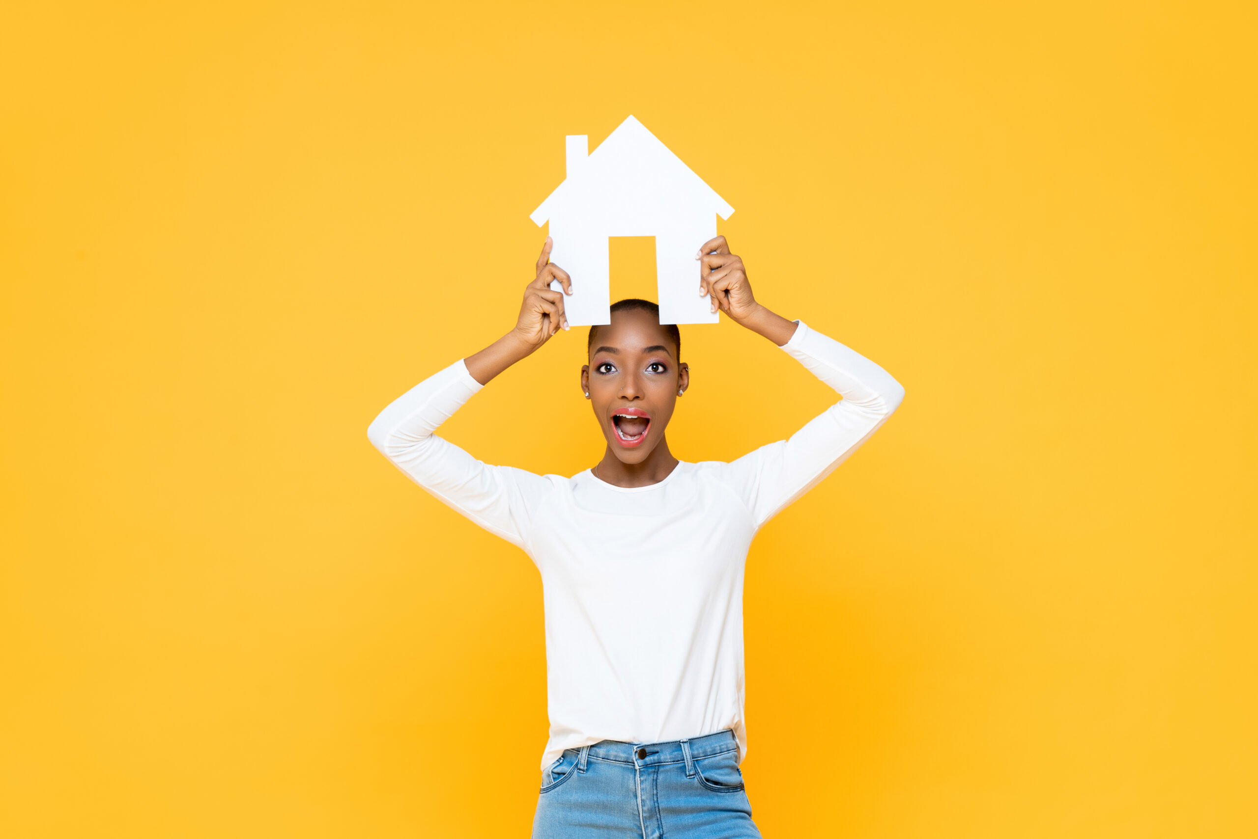 Surprised African American woman holding house sign overhead isolated on yellow background